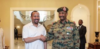 Gen. Abdel Fattah al-Burhan in a warm handshake with Abiy Ahmed